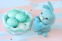 Lapin bleu-clair de Pâques cousu à la main près d'un panier de tissu avec les oeufs blanc bleu Travail manuel Carte de voeux pour photographie stock