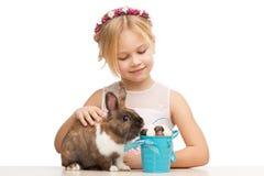 Lapin de alimentation de sourire de fille avec des oeufs de chocolat Images libres de droits