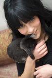 Lapin de caresse de jeune femme Photographie stock