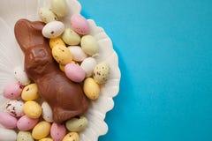 Lapin de chocolat de P?ques avec de petits oeufs color?s d'un plat sur un fond bleu L'espace de copie de vue sup?rieure photo libre de droits