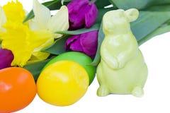 Lapin de Pâques avec des fleurs et des oeufs de source Images stock