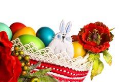 Lapin de Pâques avec des pavots et des oeufs colorés d'isolement sur le blanc Images stock