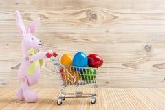 Lapin de Pâques avec un caddie complètement des oeufs de pâques colorés Images libres de droits