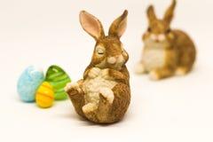 Lapin de Pâques brun somnolent avec des amis et des oeufs en verre Images stock