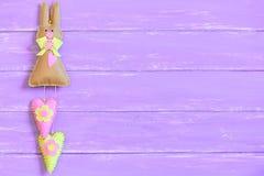 Lapin de Pâques de feutre décoré de l'arc, des boutons et des coeurs d'isolement sur le fond en bois pourpre avec l'espace de cop Image stock