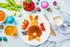 Lapin de Pâques des crêpes avec des baies Table de petit déjeuner de Pâques Fond bleu, vue supérieure image stock