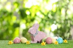 Lapin de Pâques en bois mignon et oeufs teints sur l'herbe verte photo stock