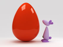 Lapin de Pâques faisant face au grand oeuf rouge Image stock