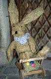 Lapin de Pâques gentil livrant des oeufs de pâques, faits par la paille photos stock