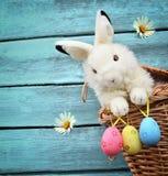 Lapin de Pâques heureux dans le panier et oeufs sur le fond bleu Photographie stock
