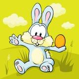 Lapin de Pâques se reposant sur l'herbe verte retenant l'oeuf Photos libres de droits