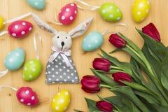 Lapin de Pâques, tulipes rouges, oeufs teints colorés sur le fond en bois Image libre de droits