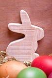 Lapin en bois et oeufs de pâques colorés Image stock