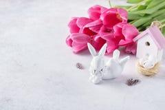 Lapin mignon, tulipes roses, petite maison et nid Joyeuses Pâques images stock