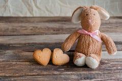 Lapin pelucheux de jouet avec des biscuits sous forme de coeurs postcard Photographie stock libre de droits