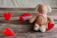 Lapin pelucheux de jouet avec des coeurs de feutre Carte postale au jour du ` s de Valentine Photos stock