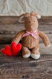 Lapin pelucheux de jouet avec des coeurs de feutre Carte postale au jour du ` s de Valentine Photographie stock libre de droits