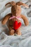 Lapin pelucheux de jouet avec des coeurs de feutre Carte postale au jour du ` s de Valentine Photographie stock