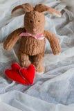 Lapin pelucheux de jouet avec des coeurs de feutre Carte postale au jour du ` s de Valentine Photo stock