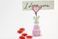 Lapin rose de figurine avec une note d'amour Photographie stock