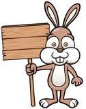 Lapin tenant le conseil en bois Photo stock