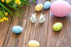Lapins avec des oeufs de pâques sur la table en bois Petit lapin de Pâques mignon Photographie stock libre de droits