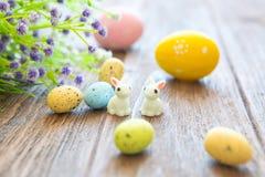 Lapins avec des oeufs de pâques sur la table en bois Petit lapin de Pâques mignon Image stock