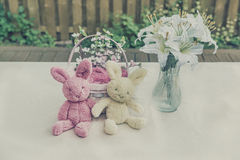 Lapins de Pâques de peluche avec le panier et les lis Image stock