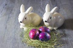 Lapins et oeufs de décoration de Pâques sur un fond gris Photographie stock