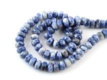 Lapis lazuli naturel de pierre gemme sur le fond blanc, perles Photos libres de droits