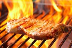 Lapje vlees bij de grill met vlammen Stock Afbeeldingen