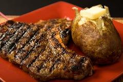 Lapje vlees en aardappel in de schil Stock Afbeelding