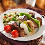 Lapje vlees en plantaardige shishkabobs met komkommersalade Royalty-vrije Stock Afbeeldingen