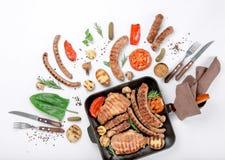 Lapje vlees en verschillende worsten en geroosterde groenten op witte bac royalty-vrije stock afbeeldingen