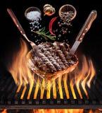 Lapje vlees het koken Conceptueel beeld Lapje vlees met kruiden en bestek onder brandende grillrooster stock afbeeldingen