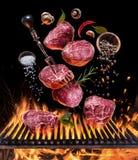 Lapje vlees het koken Conceptueel beeld Lapje vlees met kruiden en bestek onder brandende grillrooster royalty-vrije stock afbeeldingen