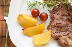 Lapje vlees met aardappels en kersentomaten Stock Foto's