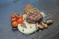 Lapje vlees met fijngestampte die aardappels, met een tak van kersentomaten worden verfraaid, croutons, plakken van donkere forel Stock Afbeeldingen