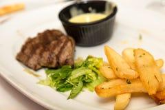 Lapje vlees met frieten en salade Stock Afbeeldingen