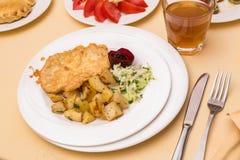 Lapje vlees met gebraden aardappels en plantaardige salade Stock Afbeelding