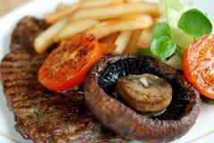 Lapje vlees met gebraden gerechten en salade Royalty-vrije Stock Afbeelding
