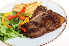 Lapje vlees met salade en gebraden gerechten Stock Afbeelding