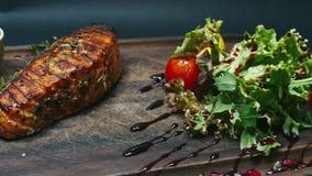 Lapje vlees met saus, tomaten en greens op een houten raad Het drijven op een schuif in 4k-resolutie stock video
