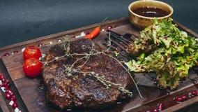 Lapje vlees met saus, tomaten en greens op een houten raad Het drijven op een schuif in 4k-resolutie stock footage