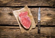 Lapje vlees ruw vlees met een mes Op houten achtergrond Royalty-vrije Stock Afbeeldingen