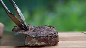 Lapje vlees uit grill op scherpe raad wordt gesneden die stock footage