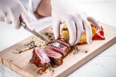 Lapje vlees van het chef-kok het scherpe rundvlees Stock Afbeeldingen