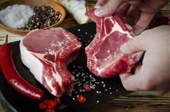 lapje vlees van het hand het zoute vlees Ruw marmervleeslapje vlees, peper, kruiden, knoflook, oude houten achtergrond Ruimte voo stock foto