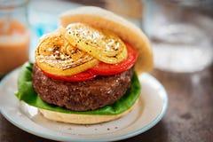 Lapje vleeshamburger met groene sla, plakken van tomaten en geroosterde uien - de zoete Spaanse pepers dompelen onder Stock Foto's