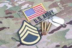 Lapp för sergeant för USA-ARMÉ frodig, flaggalapp, med hundetiketten och 5 56 mmrundor på likformign Arkivfoton